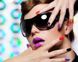 Woman with multicolored manicure and fashion stylish sunglasses